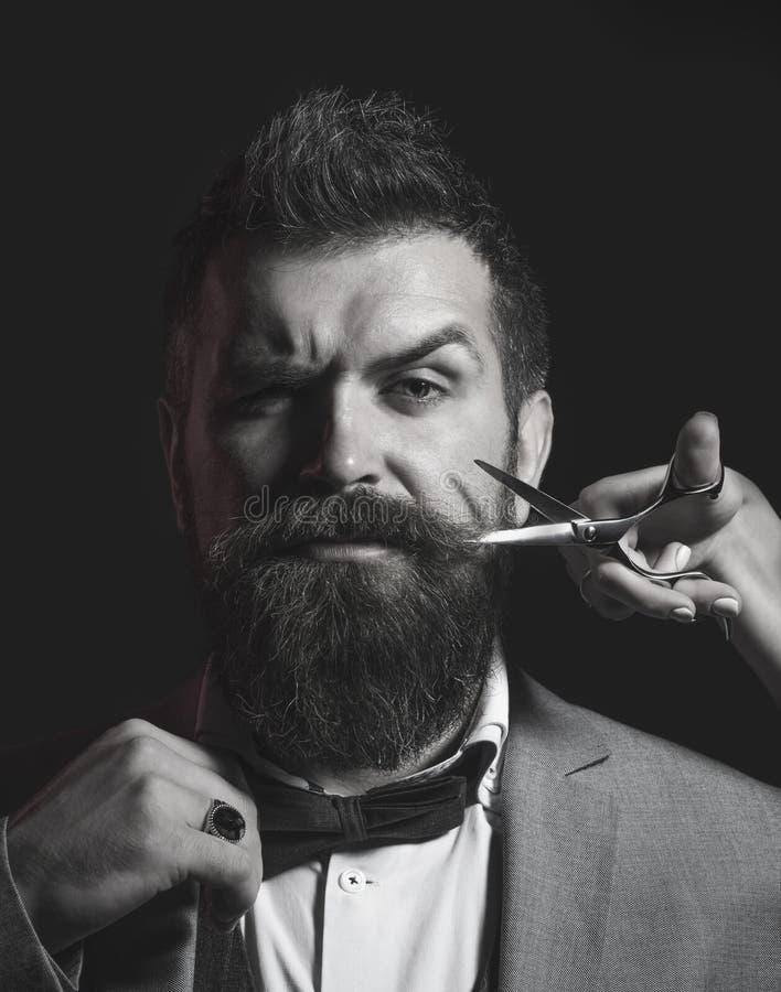 Homem farpado, barba longa, moderno brutal, caucasiano com bigode Corte de cabelo dos homens na barbearia Tesouras do barbeiro, e imagem de stock royalty free