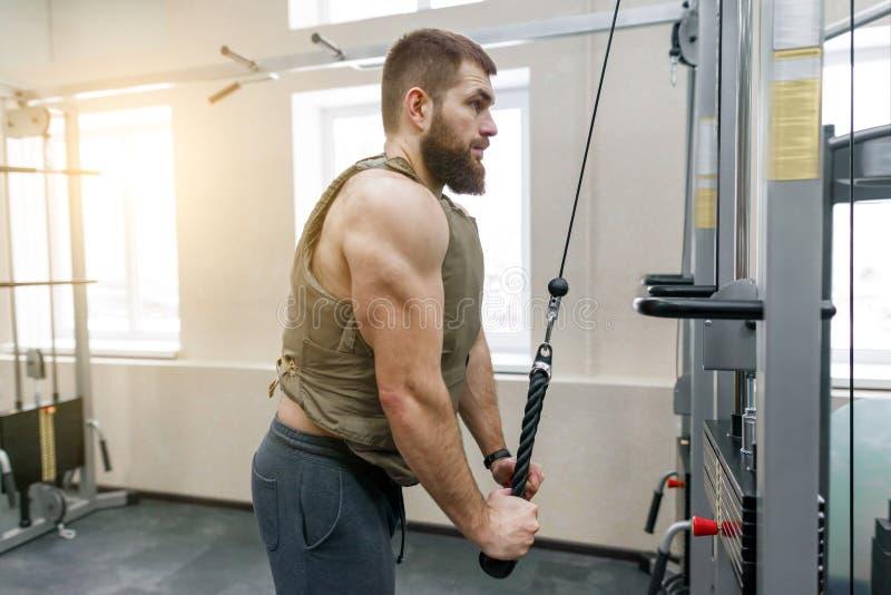 Homem farpado caucasiano muscular que faz os exercícios vestidos na veste tornada mais pesada no gym, estilo militar foto de stock