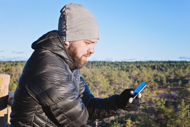 Homem farpado caucasiano que olha o smartphone contra o céu azul foto de stock royalty free