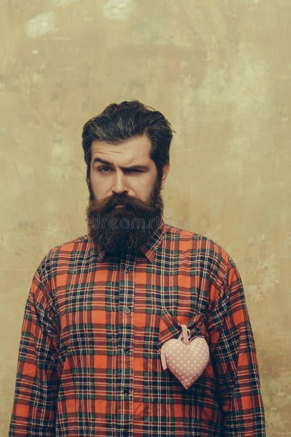 Homem farpado com a barba com coração rosado de matéria têxtil na camisa foto de stock royalty free