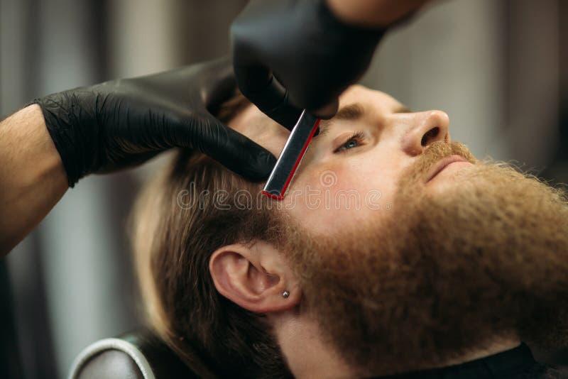 Homem farpado com a barba longa que obtém o cabelo à moda que barbeia, corte de cabelo, com a lâmina pelo barbeiro no barbeiro imagem de stock