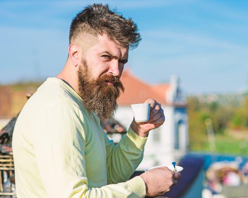Homem farpado com caneca do café, café das bebidas O homem com barba e bigode na cara restrita bebe o café, fundo urbano foto de stock