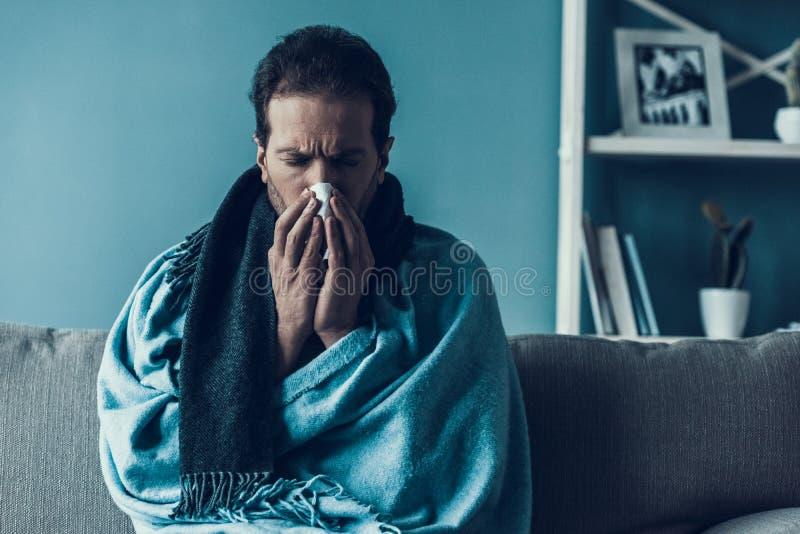 Homem farpado com o conduto que senta-se no sofá em casa foto de stock royalty free