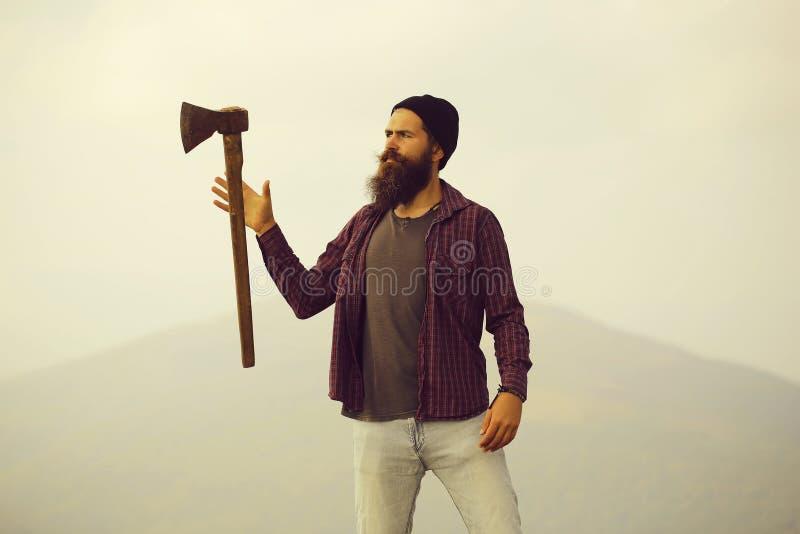Homem farpado com o machado na montanha foto de stock
