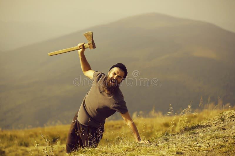 Homem farpado com o machado na montanha imagens de stock royalty free