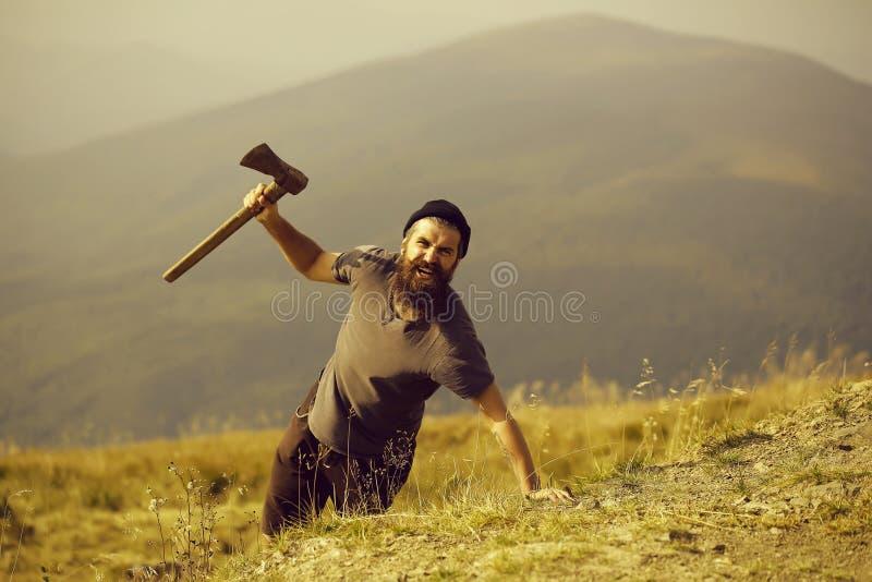 Homem farpado com o machado na montanha imagem de stock royalty free