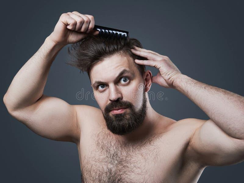 Homem farpado com pente foto de stock