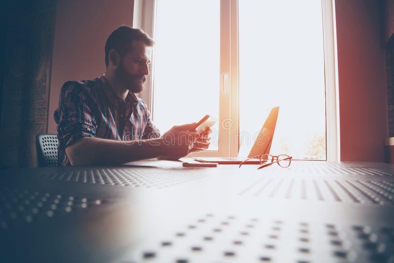 Homem farpado com portátil e a tabuleta digital