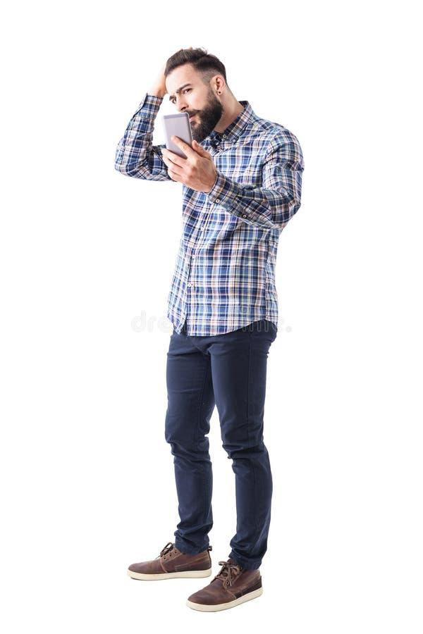 Homem farpado considerável com mão no cabelo que ajusta o penteado usando a reflexão do telefone celular como o espelho fotografia de stock royalty free