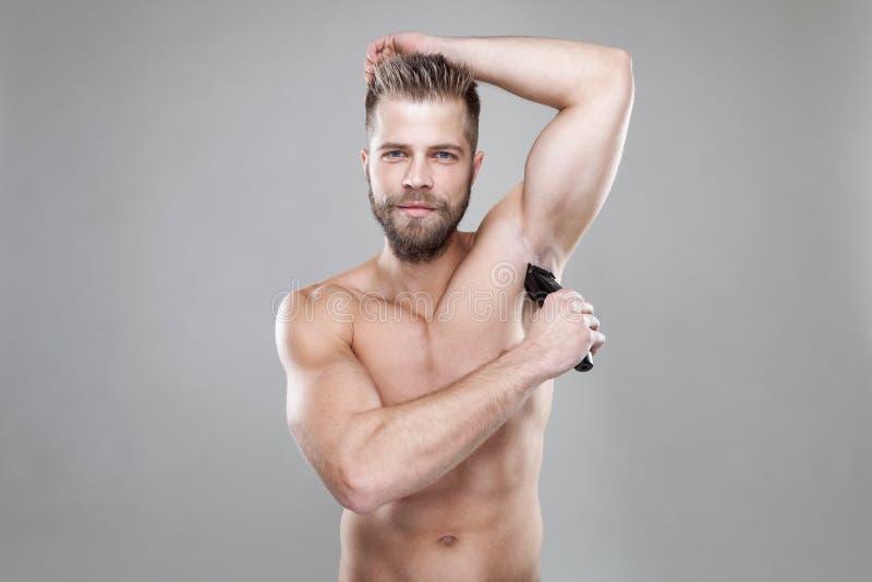 Homem farpado considerável com um ajustador que barbeia fora do cabelo do corpo imagens de stock royalty free