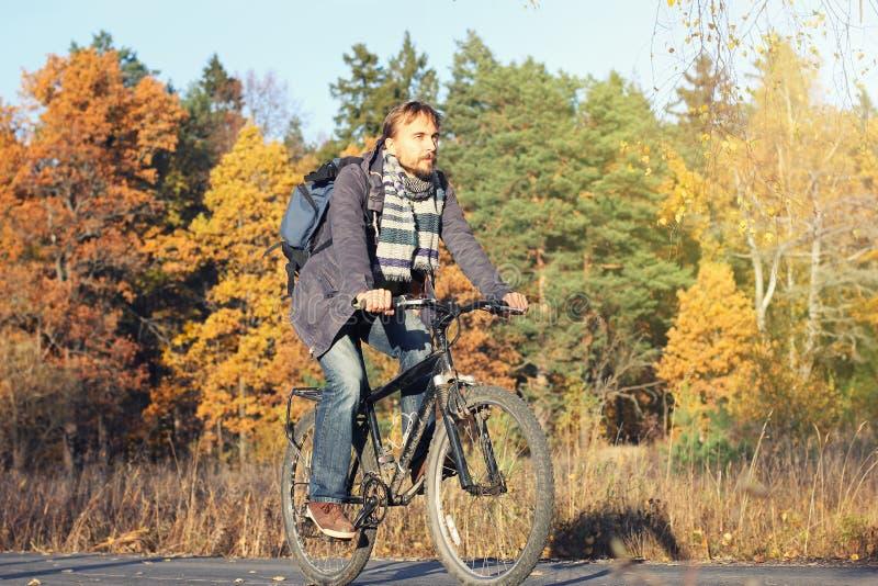 Homem farpado consider?vel do moderno no vestu?rio desportivo com a bicicleta da equita??o da trouxa no outono bonito da descober imagem de stock