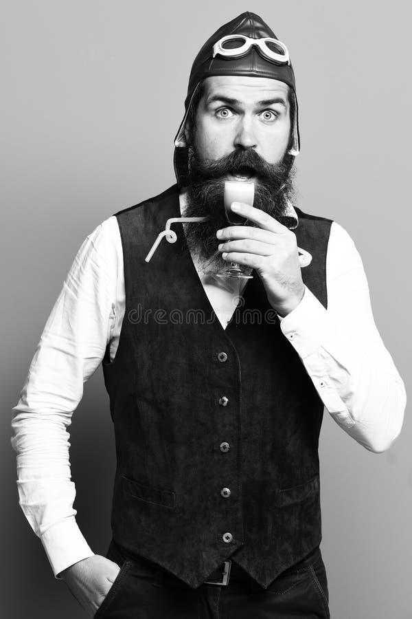 Homem farpado considerável do piloto ou do aviador com barba longa e bigode na cara surpreendida que prova o vidro do tiro alcoól fotos de stock royalty free