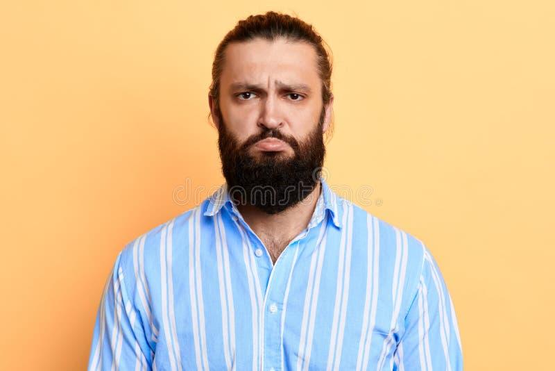 Homem farpado considerável duvidoso nervoso que olha de sobrancelhas franzidas suas sobrancelhas imagem de stock