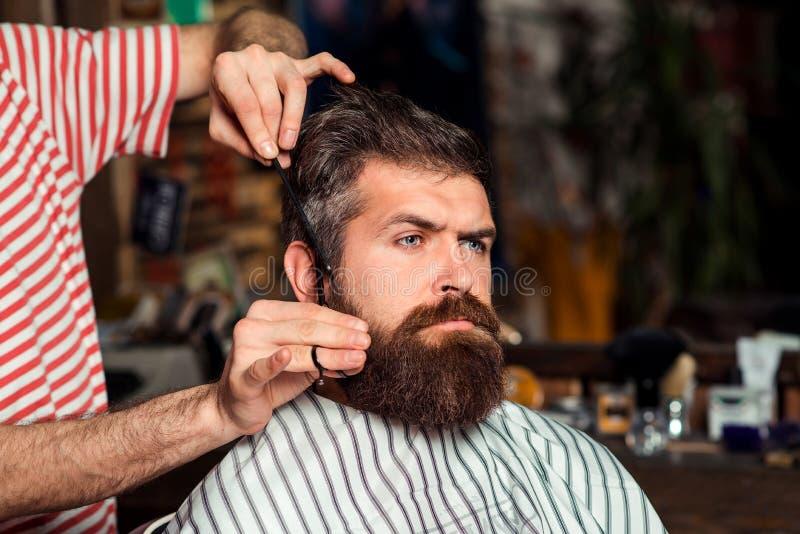 Homem farpado considerável na barbearia Cliente do serviço do barbeiro no barbeiro Hora para o corte de cabelo novo Fazendo o olh foto de stock