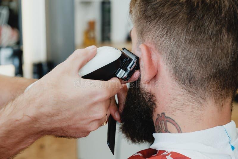 Homem farpado considerável no barbeiro O barbeiro corta o cabelo com elege fotos de stock