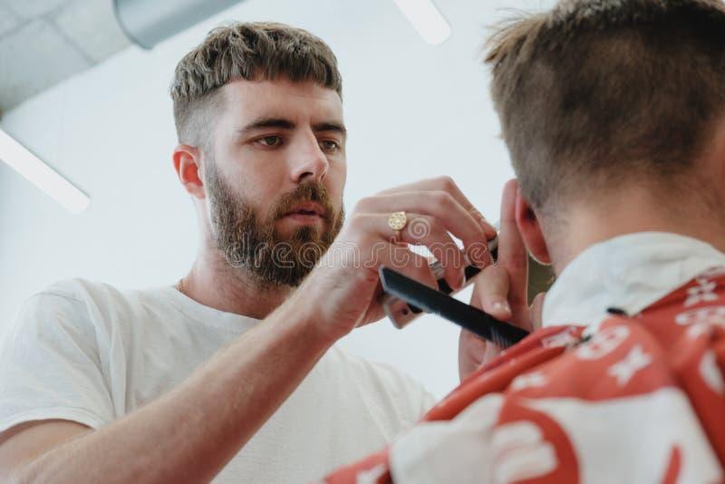 Homem farpado considerável no barbeiro O barbeiro corta o cabelo com elege imagem de stock