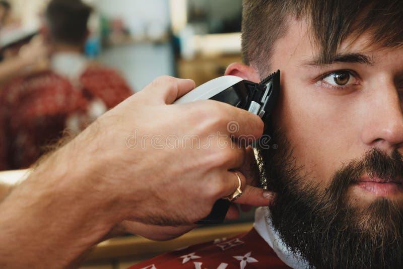 Homem farpado considerável no barbeiro O barbeiro corta o cabelo com elege imagens de stock