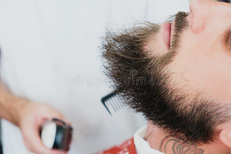 Homem farpado considerável no barbeiro O barbeiro escova e corta o cabelo imagens de stock