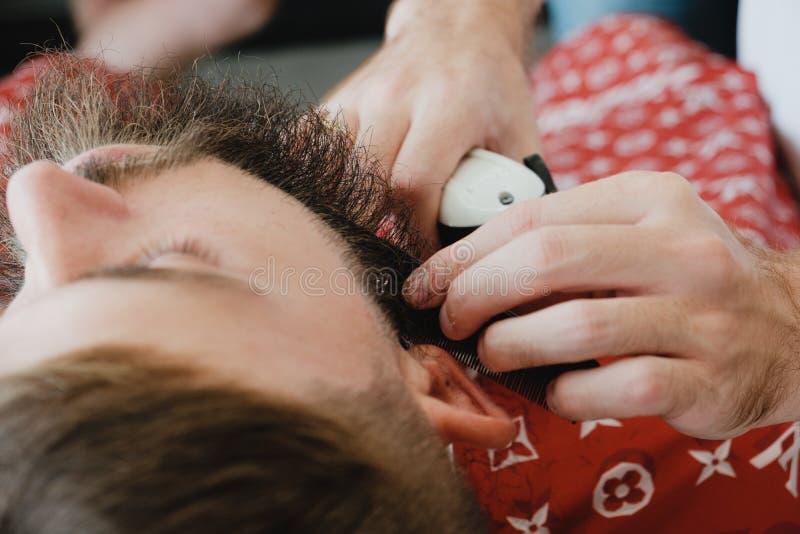 Homem farpado considerável no barbeiro O barbeiro escova e corta o cabelo imagem de stock