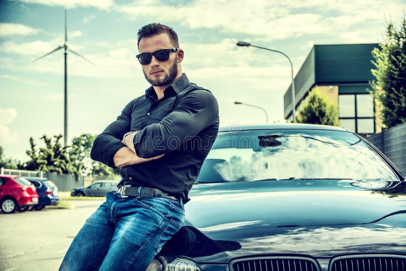 Homem farpado considerável no carro lustrado nos óculos de sol imagem de stock royalty free