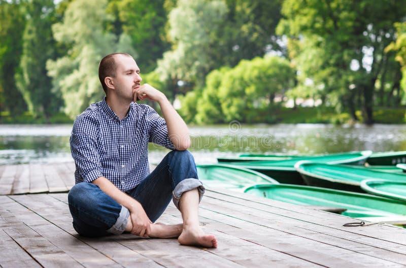 Homem farpado considerável novo que senta-se no cais de madeira, no relaxamento e no pensamento fotografia de stock