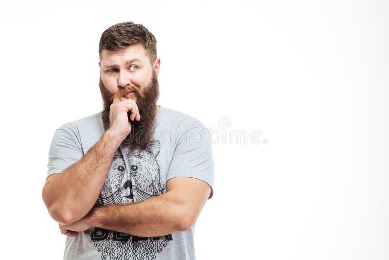 Homem farpado considerável pensativo que está com as mãos dobradas e o pensamento imagens de stock