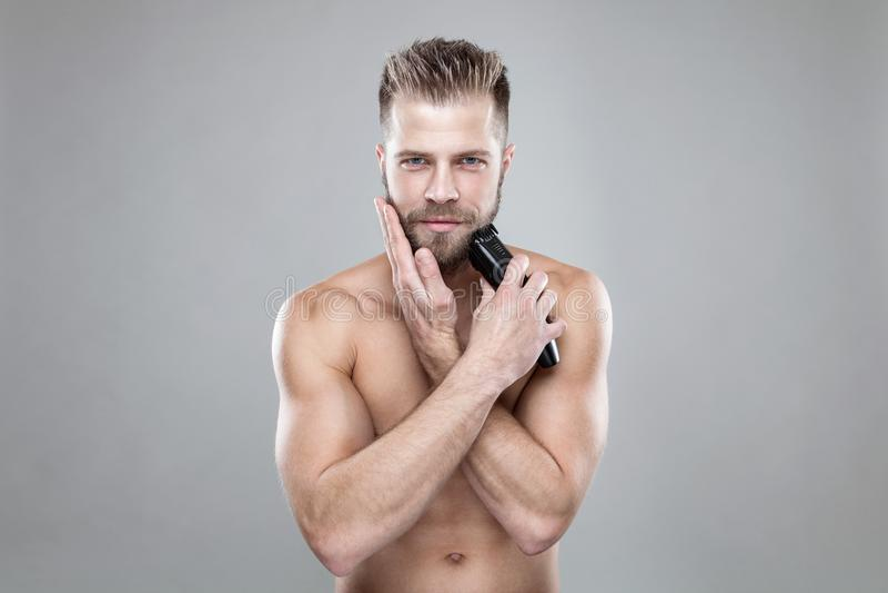 Homem farpado considerável que apara sua barba com um ajustador imagem de stock royalty free