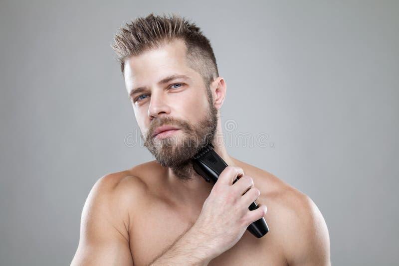 Homem farpado considerável que apara sua barba com um ajustador fotografia de stock