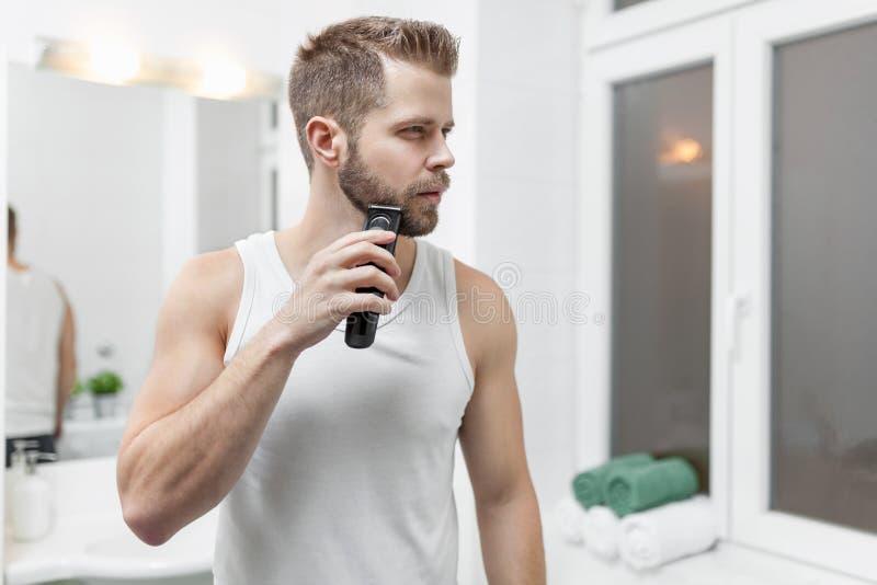 Homem farpado considerável que apara sua barba com um ajustador imagens de stock royalty free