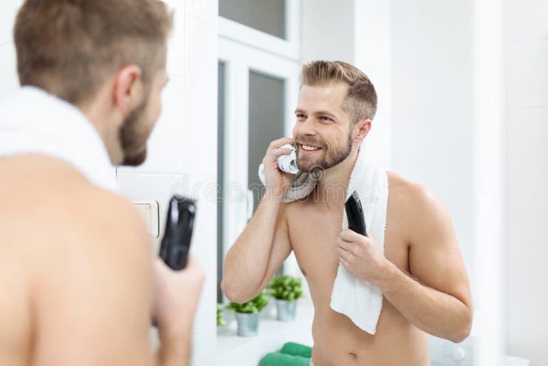 Homem farpado considerável que apara sua barba com um ajustador imagem de stock