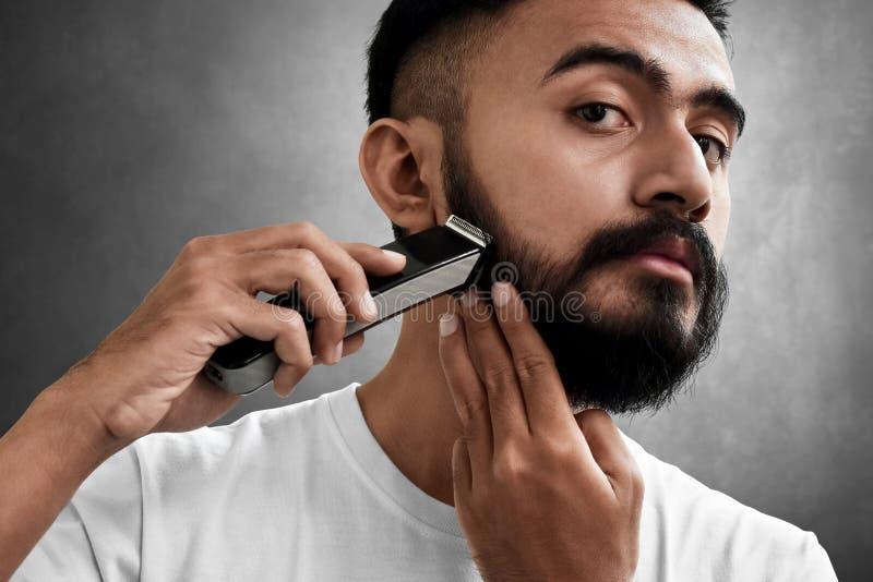 Homem farpado considerável que barbeia sua barba imagem de stock
