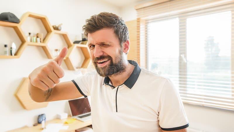 Homem farpado considerável que dá a piscadela que mostra o polegar acima imagem de stock