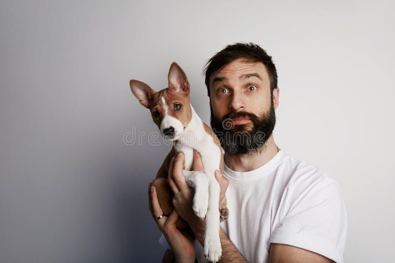 Homem farpado considerável que guarda seu cão de cachorrinho do basenji nos braços com amor e que joga com ele, contra um fundo b imagens de stock royalty free