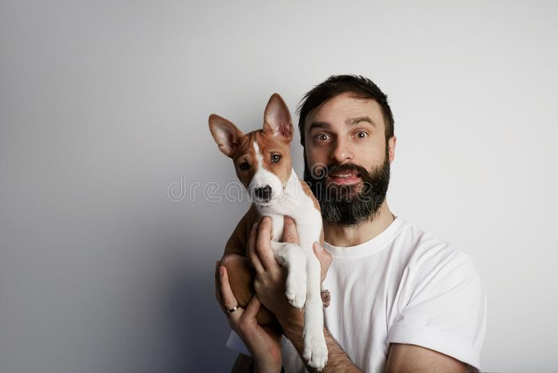 Homem farpado considerável que guarda seu cão de cachorrinho do basenji nos braços com amor e que joga com ele, contra um fundo b fotografia de stock