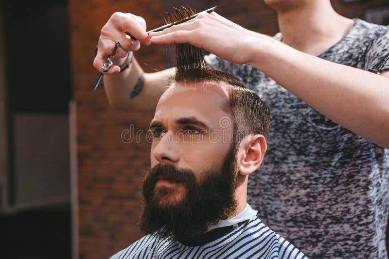 Homem farpado considerável que tem o corte de cabelo com pente e tesouras fotos de stock royalty free