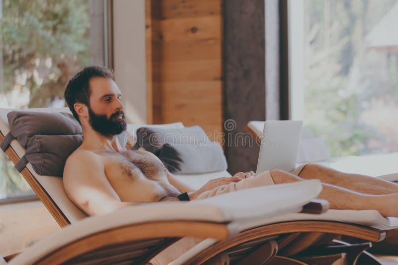 Homem farpado considerável que usa o laptop ao descansar no hotel dos termas Homem que relaxa após o dia difícil no salão de bele imagens de stock royalty free