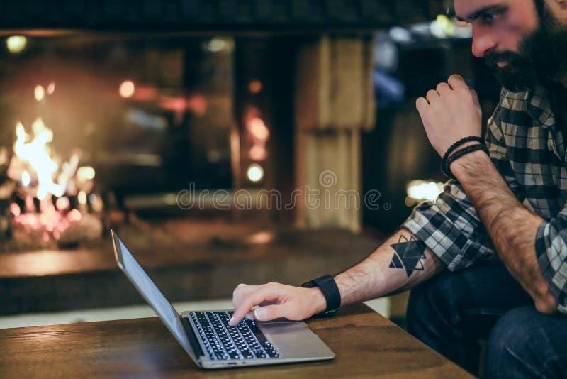 Homem farpado considerável que usa o laptop móvel ao descansar no hotel da entrada Homem que usa o dispositivo eletrônico borrado fotos de stock