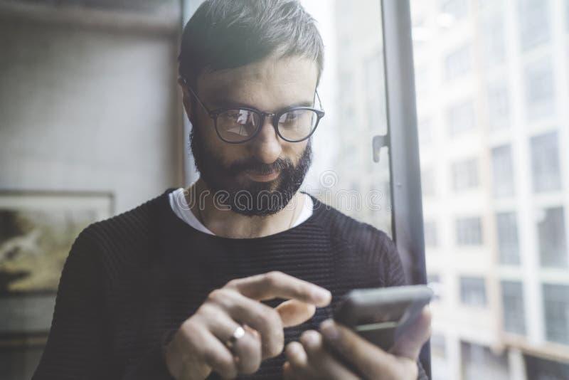 Homem farpado considerável que usa o smartphone móvel para o Internet surfando da Web Homem que usa o dispositivo no estúdio mode foto de stock
