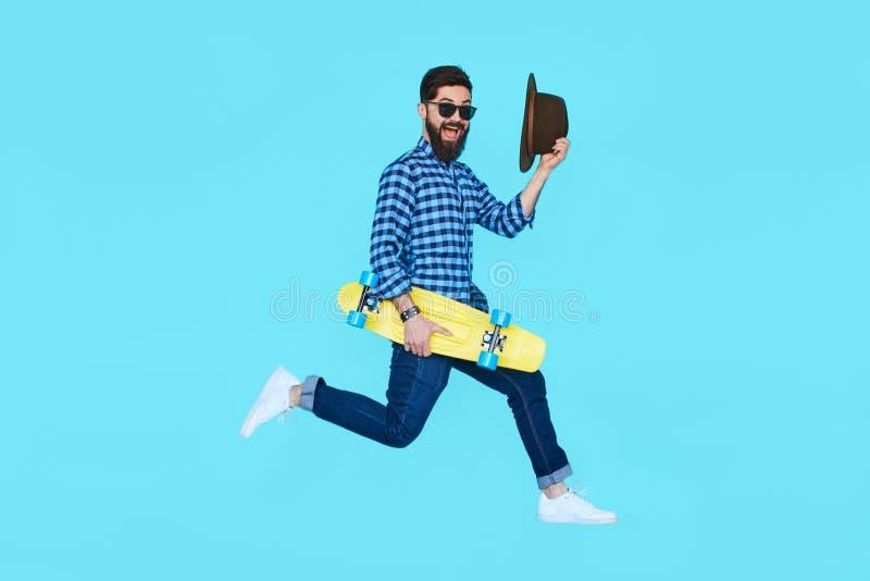 Homem farpado consideravelmente novo que salta com skate amarelo imagem de stock