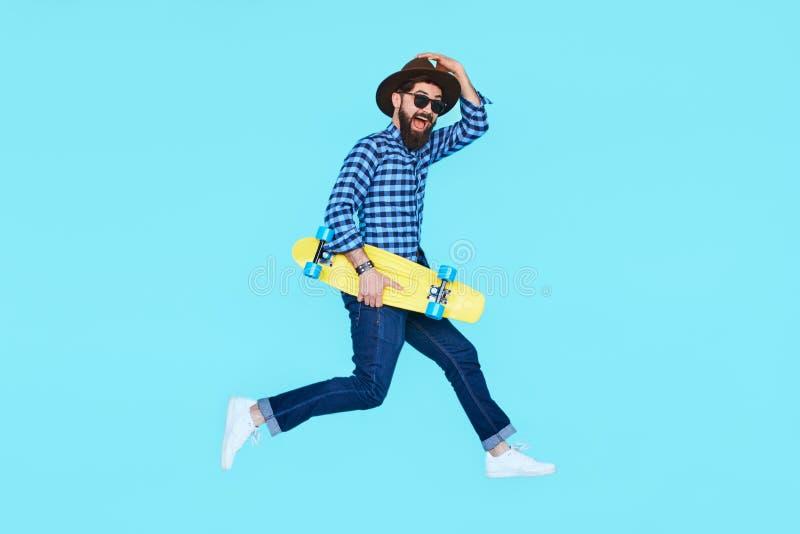 Homem farpado consideravelmente novo que salta com skate amarelo foto de stock