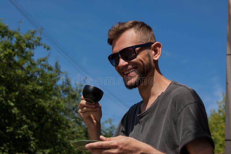 Homem farpado de sorriso com a xícara de café em sua mão contra o céu azul no dia de verão ensolarado imagem de stock