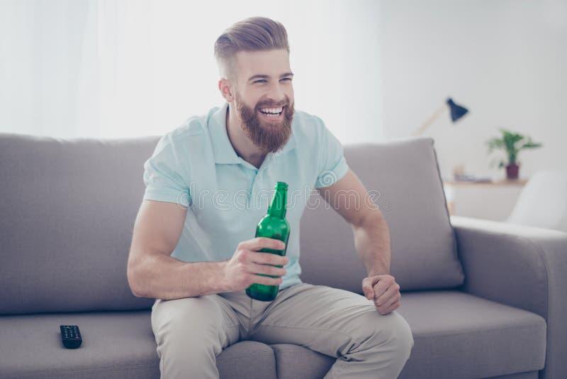 Homem farpado de sorriso feliz novo na roupa ocasional que senta-se no sof foto de stock royalty free