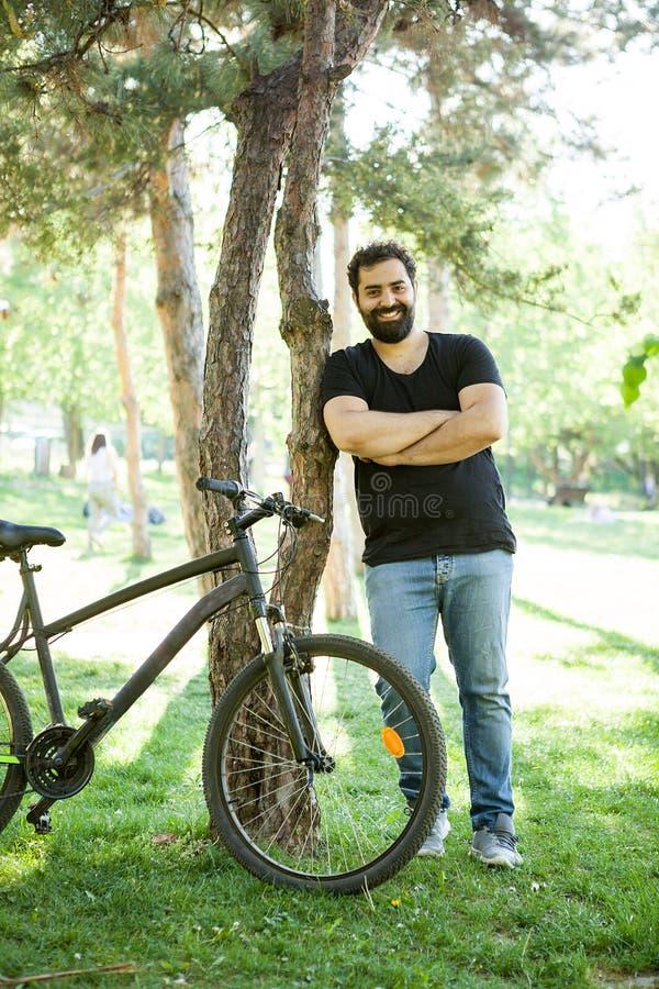 Homem farpado de sorriso que inclina-se em uma árvore no parque imagem de stock royalty free