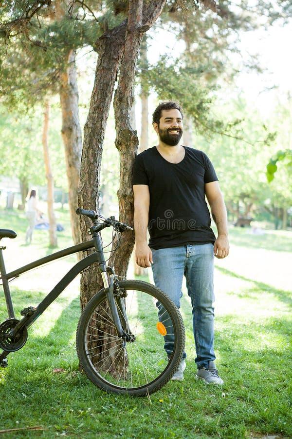 Homem farpado de sorriso que inclina-se em uma árvore no parque fotografia de stock royalty free