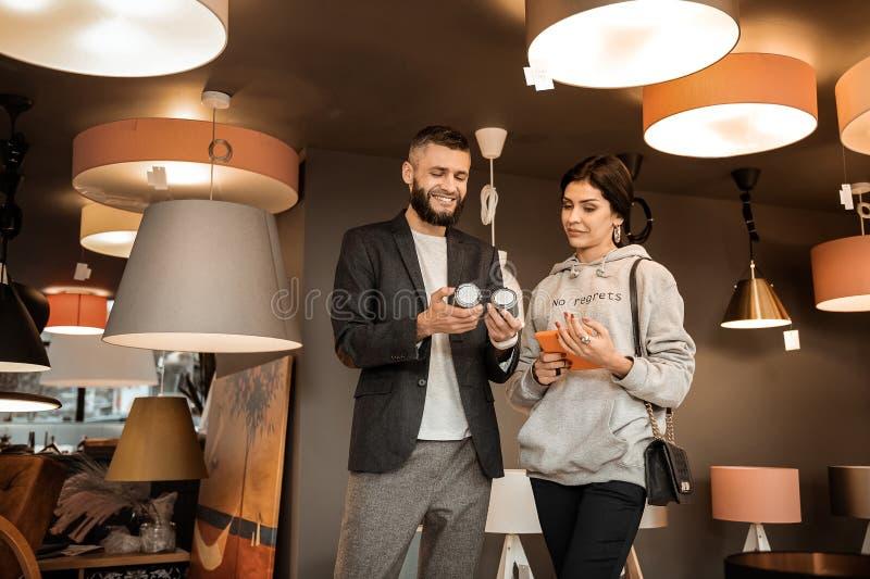 Homem farpado de sorriso que leva lâmpadas lisas quando sua tabuleta da terra arrendada da esposa imagem de stock