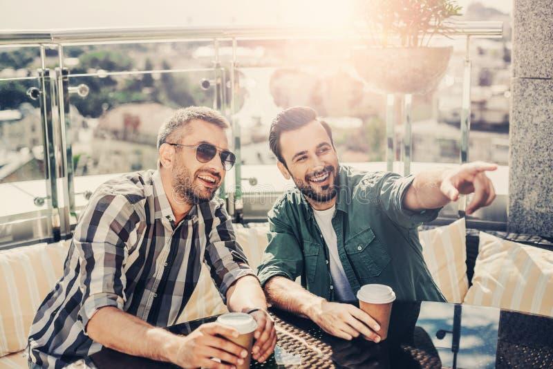 Homem farpado de sorriso que senta-se na tabela com amigo e que aponta em algo fotos de stock
