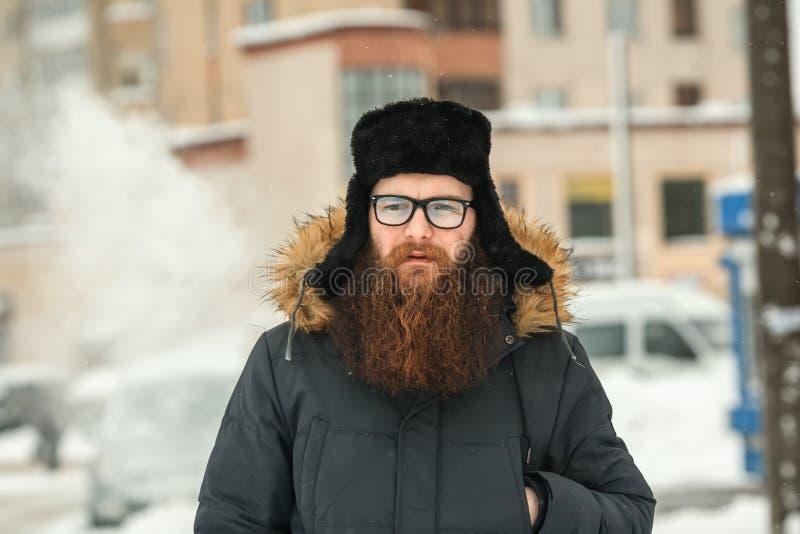 Homem farpado de Vape na vida real Indivíduo com a grande barba nos vidros e um tampão preto que vaping um cigarro eletrônico imagem de stock royalty free