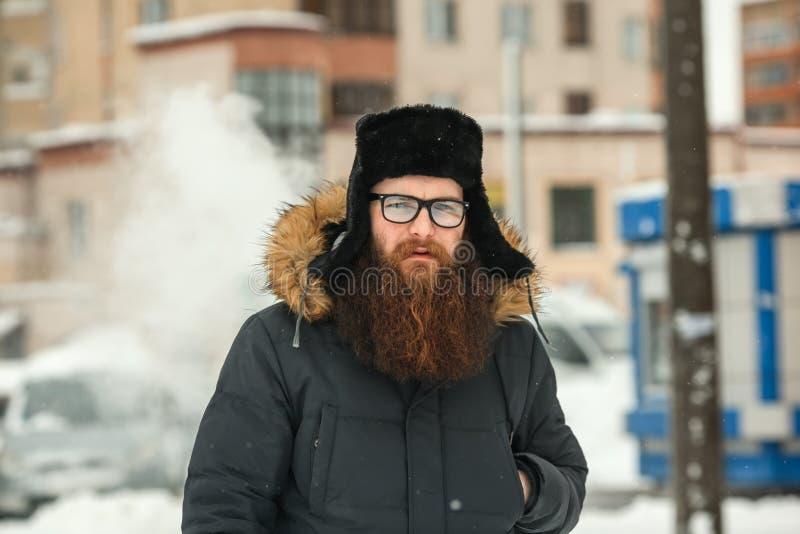 Homem farpado de Vape na vida real Indivíduo com a grande barba nos vidros e um tampão preto que vaping um cigarro eletrônico imagens de stock royalty free