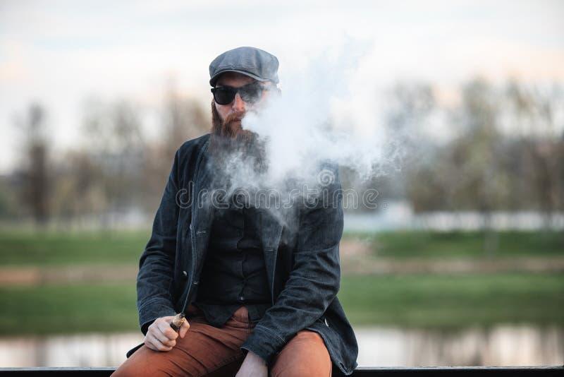 Homem farpado de Vape na vida real Retrato do indivíduo novo com a grande barba em um tampão e nos óculos de sol que vaping um ci imagem de stock royalty free