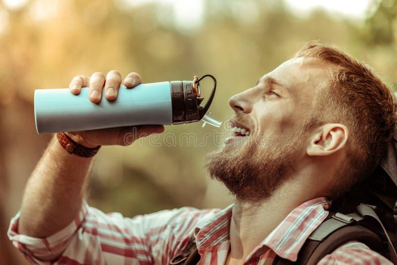 Homem farpado deleitado agradável que guarda uma garrafa de garrafa térmica fotos de stock